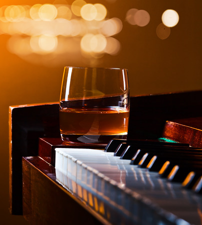 piano closeup: glass with whiskey on a old piano Stock Photo