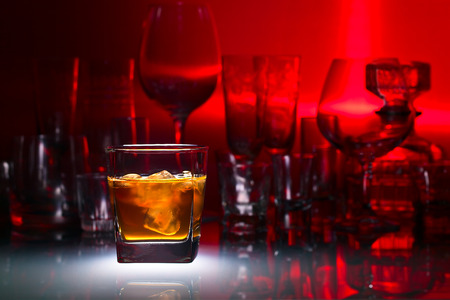 horizontal bar: whiskey with ice on glass table in bar Stock Photo