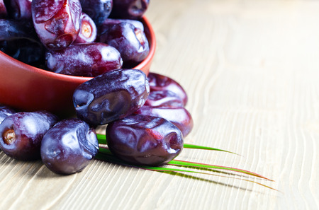 juicy dates in a brown dish on wooden table Stock Photo
