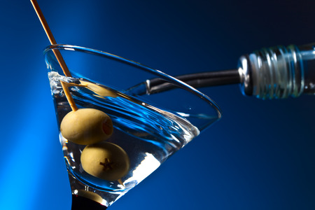 martini glass: dry martini with green olives , focus on a berry Stock Photo