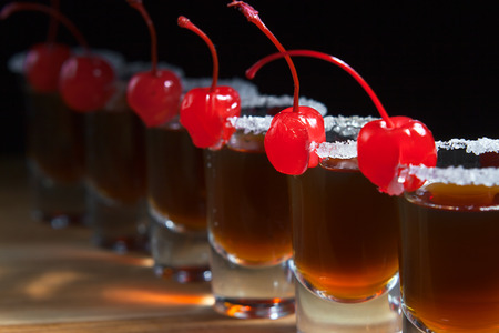 alcoholic drink: alcoholic drink with cherries on wooden table