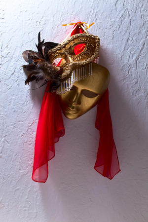 Two golden Venetian masks on a old wall photo