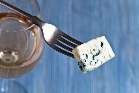 gorgonzola: The Gorgonzola cheese on a fork and sweet wine