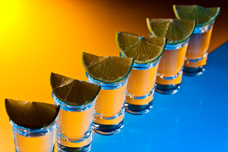 alcoholic drink: alcoholic drink with lime on a glass table