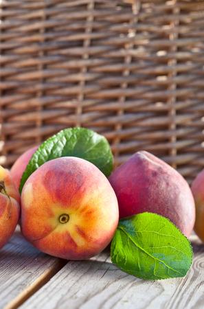 vertica: juicy peaches on wooden table in garden