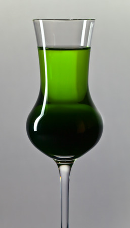 alcoholic drink: green alcoholic drink on a grey background