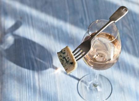 queso blanco: El queso Gorgonzola en un tenedor y el vino dulce