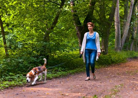 mujer perro: Mujer con perro caminando en el parque Foto de archivo