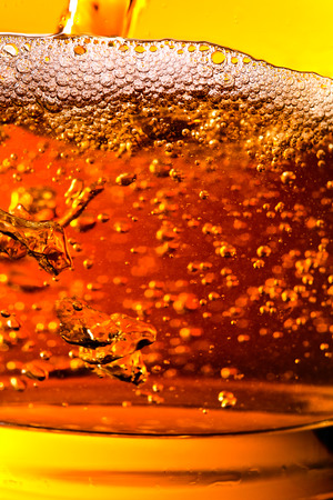 alcoholic beverage: detail of an alcoholic beverage on yellow background Stock Photo