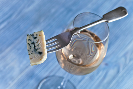 The Gorgonzola cheese on a fork and sweet wine