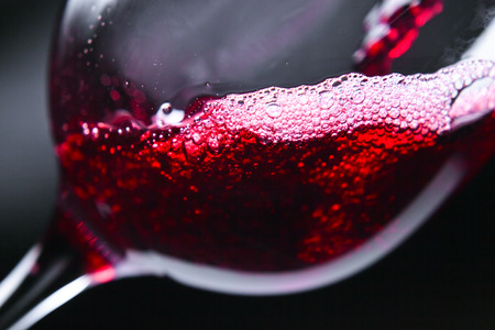 pouring: Red wine in wineglass on dark