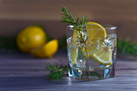 alcoholic drink: alcoholic drink with lemon and ice on a old wooden table Stock Photo