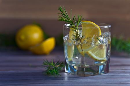 bebidas alcohÓlicas: bebida alcohólica con limón y hielo en una mesa de madera vieja Foto de archivo