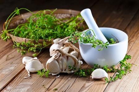 ajo: ajo y hierbas de cocina en la mesa de madera