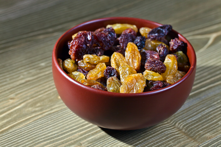 grape fruit: raisins in a brown dich on wooden table
