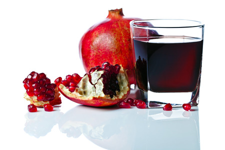 a pomegranate: ripe pomegranate and juice isolated on a white reflexive background