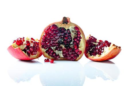 pomegranate: ripe pomegranate isolated on a white reflexive background