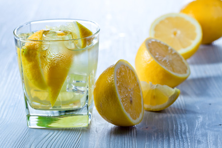 gin and tonic with lemon and ice on wooden table