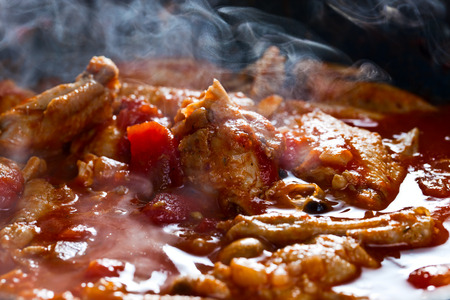 stewed: Stewed chicken with spices in a tomato sauce Stock Photo