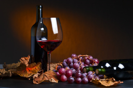red wine with grapes and vine leaves Imagens
