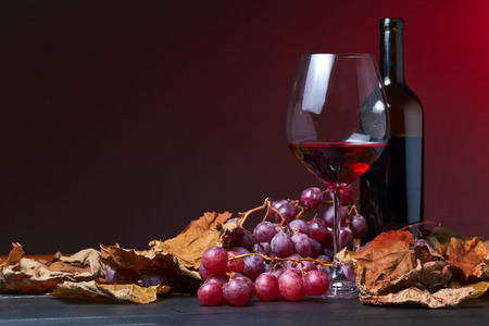 red wine with grapes and vine leaves Standard-Bild