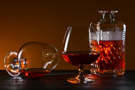 snifter: Snifter with brandy on black wooden table