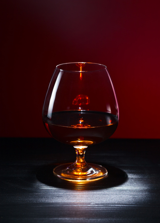 restaurant tables: Snifter with brandy on black wooden table