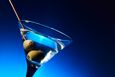 martini glasses: dry martini with olives ,focus on a berry