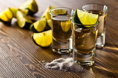 drinks: tequila with salt and lime on old wooden table