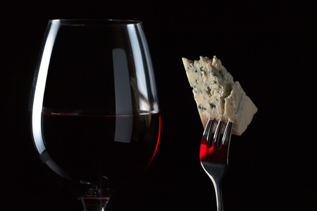 Cheese on a fork and red wine on black background