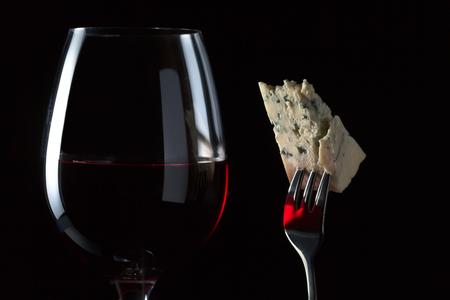 manjar: Queso en un vino tenedor y rojo sobre fondo negro Foto de archivo