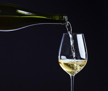 Weißwein in ein Weinglas gegossen. Standard-Bild - 48672859