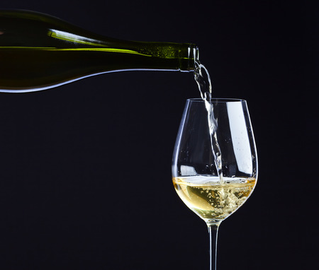 Witte wijn wordt gegoten in een wijnglas. Stockfoto