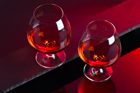 snifter: Snifter with brandy on a red background
