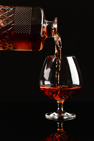 snifter: Snifter with brandy on a black background