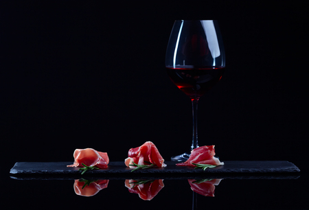 jamon with rosemary and red wine in black glass