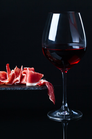 jamon with red wine on  a black background