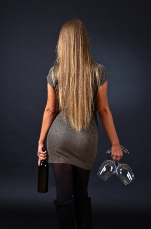 glamour hair: young beautiful woman with wine on black background