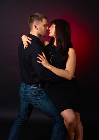 The young couple dancing on datk background