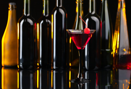 sweet vermouth: Cocktail with cherry on black table in bar