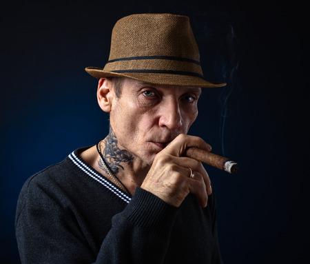 hombre fumando puro: el hombre con el cigarro fumar sombrero, tiro del estudio