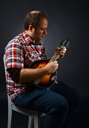 mandolin: portrait of musician with mandolin , studio shot