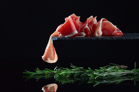 jamon: jamon with rosemary on  a black background