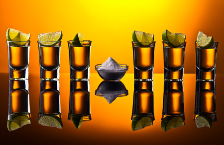 reflective background: Gold tequila and lime on a black reflective background Stock Photo