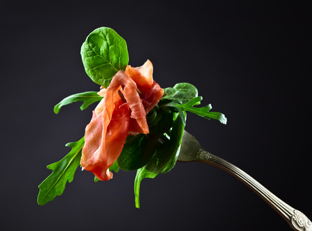 and delicious food: jamon with spinach and  arugula on dark background