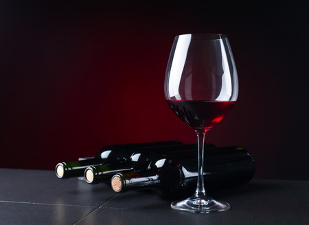 bottles and glass of red wine on  black table