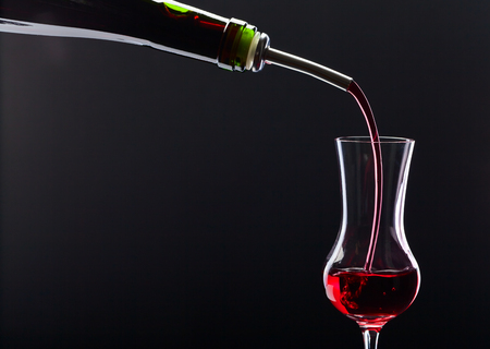 alcoholic drink: bottle and glass with alcoholic drink on black background