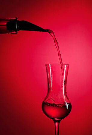 alcoholic drink: bottle and glass with alcoholic drink on red background Stock Photo