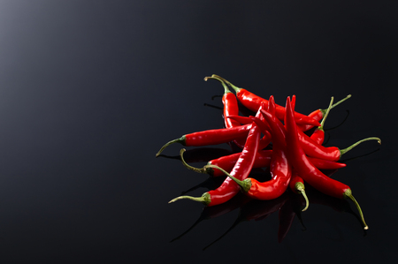beam of red chilli pepper on black background