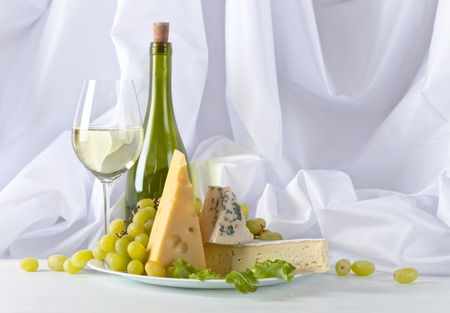 cheeses with grapes and wine on white table